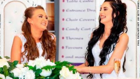 Không giấu nổi niềm hạnh phúc, Robyn Peoples và bạn đời Sharni Edwards cho biết ước mơ của họ đã trở thành sự thật khi chính thức kết hôn vào đúng dịp kỷ niệm 6 năm hẹn hò. Hai cô gái đầu tiên kết hôn đồng giới ở Bắc Ireland - 2 Họ là cặp đôi đồng giới đầu tiên kết hôn ở Bắc Ireland sau khi luật pháp nước này chính thức công nhận hôn nhân đồng giới từ ngày 10/2. Hai cô gái đầu tiên kết hôn đồng giới ở Bắc Ireland - 3 Hai cô gái trao nhau nụ hôn ngọt ngào trong hôn lễ diễn ra tại khách sạn Loughshore ở C