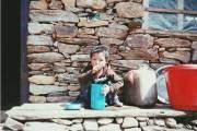 Một em bé ngồi chơi trước hiên nhà