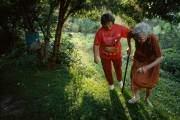 Một phụ nữ giúp mẹ chồng đi lại trong khu vườn của gia đình năm 1993 tại Kentucky, Mỹ.