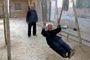"""Hai vợ chồng ông Diêu Tự Cương, tỉnh Sơn Tây, đều đã ở tuổi """"thất thập cổ lai hy"""" nhưng vẫn hồn nhiên chơi xích đu cùng nhau trong sân nhà."""
