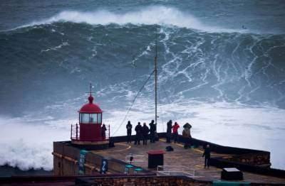 Người dân chứng kiến một cơn sóng lớn ở Praia do Norte, bờ biển phía Bắc ở làng chài Nazare, Bồ Đào Nha. (Nguồn: Sputniknews)