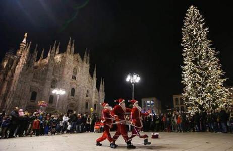 Những nghệ sĩ mặc trang phục Ông già Noel biểu diễn trước thánh đường Duomo ở thành phố Milan, Italy.