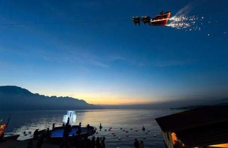 Ông già Noel ngồi trên chiếc xe tuần lộc chạy bằng cáp treo vẫy chào với khách thăm quan ở hồ Geneva tại hội chợ Giáng sinh lần thứ 20 ở Montreux, Thụy Sĩ.