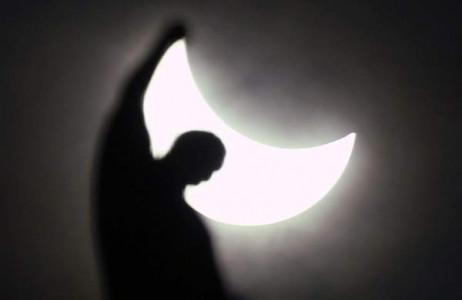 Hiện tượng nhật thực nhìn từ phía sau một bức tượng nhà thờ Gothic Duomo ở Milan, Italy ngày 20/3
